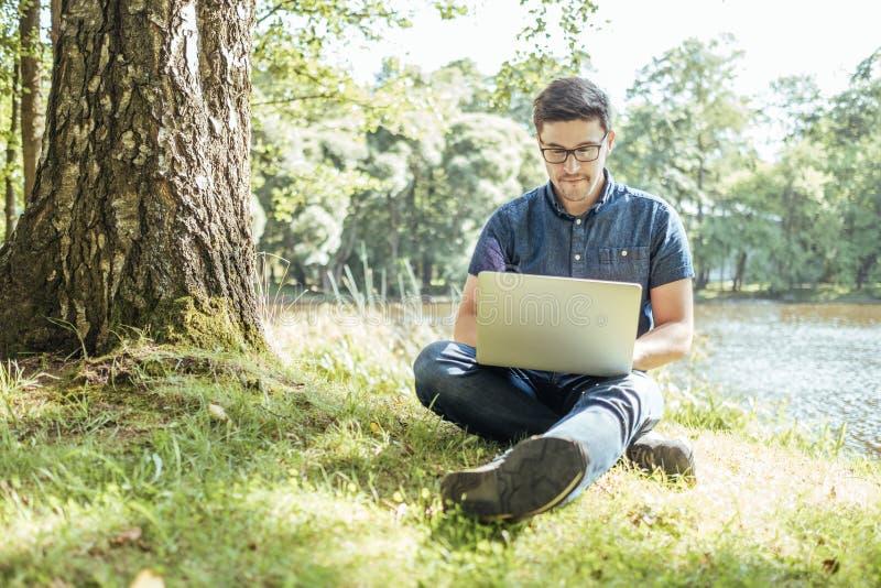 Hombre joven con la sentada al aire libre del ordenador portátil en la hierba foto de archivo