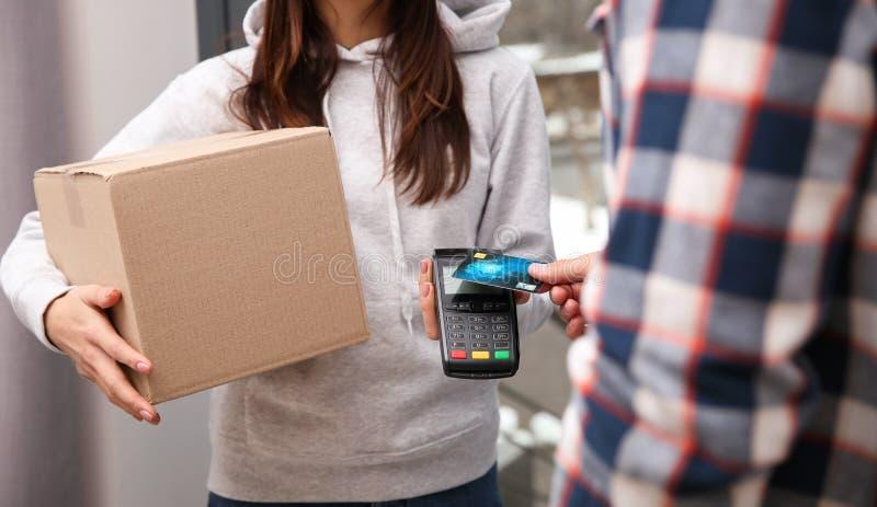 Hombre joven con la tarjeta de crédito usando el terminal del banco para el pago de la entrega en la entrada imagen de archivo libre de regalías