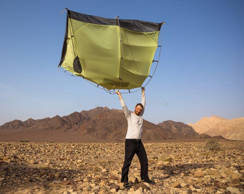 Hombre joven con la tienda en paisaje del desierto imagen de archivo