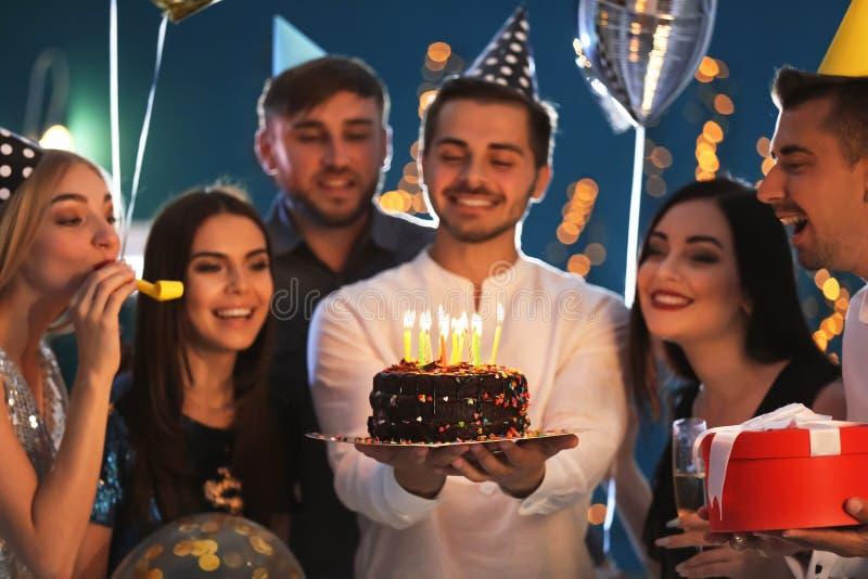 Hombre joven con la torta sabrosa y sus amigos en la fiesta de cumpleaños en club imagen de archivo