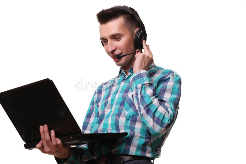 Hombre joven con las auriculares que sostienen el ordenador portátil - hombre del centro de atención telefónica con hea fotografía de archivo libre de regalías