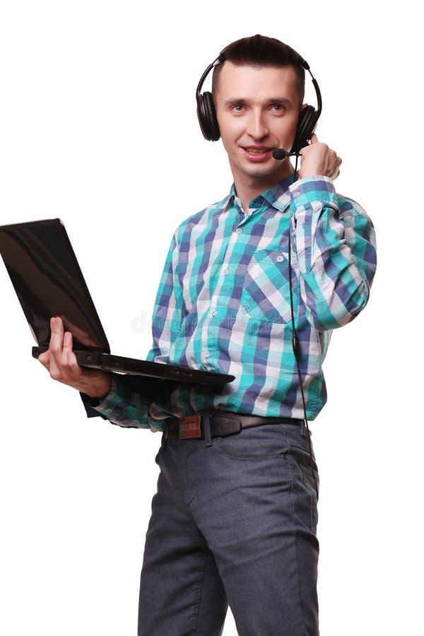 Hombre joven con las auriculares que sostienen el ordenador portátil - hombre del centro de atención telefónica con hea imágenes de archivo libres de regalías