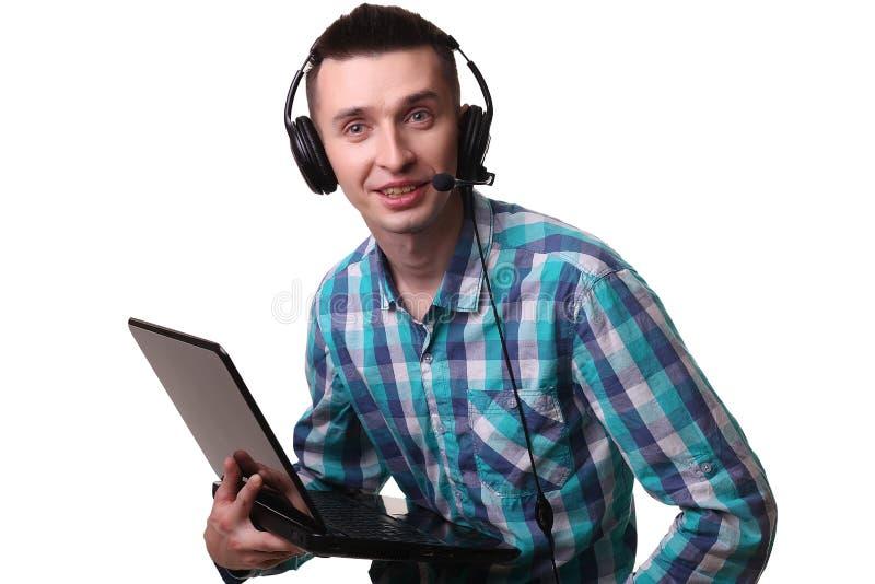 Hombre joven con las auriculares que sostienen el ordenador portátil - hombre del centro de atención telefónica con hea imagen de archivo