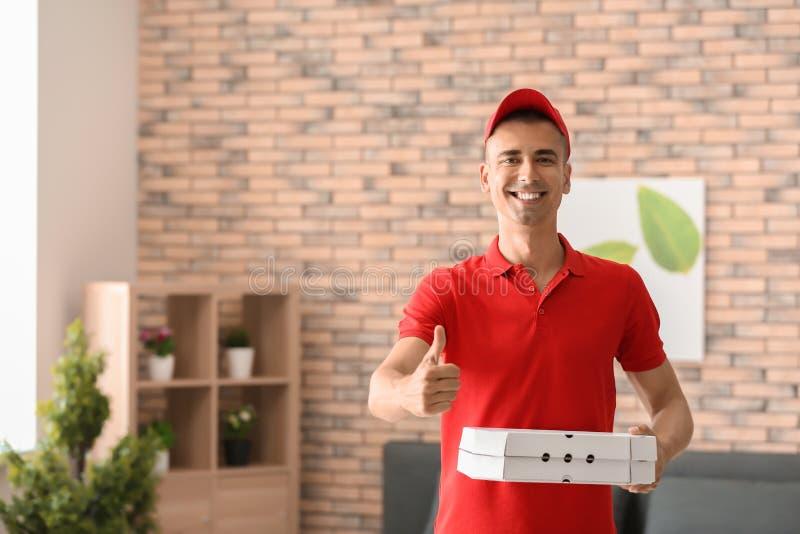 Hombre joven con las cajas de la pizza que muestran gesto del pulgar-para arriba dentro Servicio de entrega de la comida fotografía de archivo libre de regalías