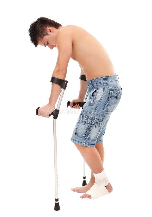 Hombre joven con las muletas imagen de archivo