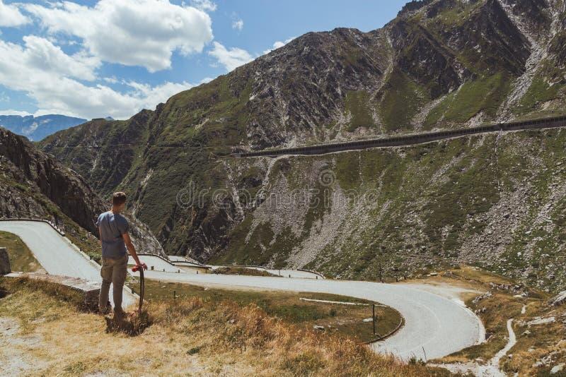 Hombre joven con longboard que comtempla un camino con curvas que desciende en un valle foto de archivo