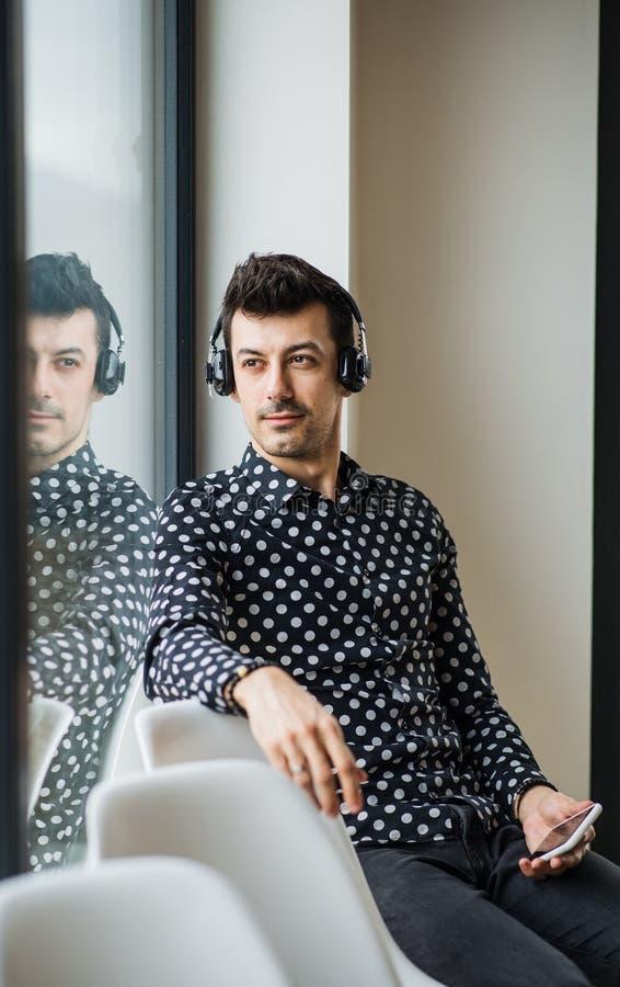 Hombre joven con los auriculares que se sientan por la ventana, escuchando la música fotografía de archivo