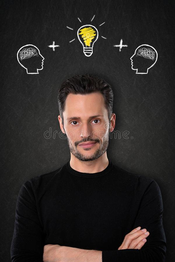 Hombre joven con los brazos cruzados, las cabezas con los cerebros y bulbo-idea ligera en un fondo de la pizarra fotos de archivo libres de regalías