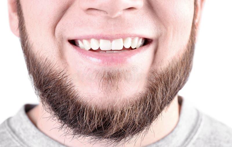 Hombre joven con los dientes sanos que sonríe en el fondo blanco fotografía de archivo libre de regalías
