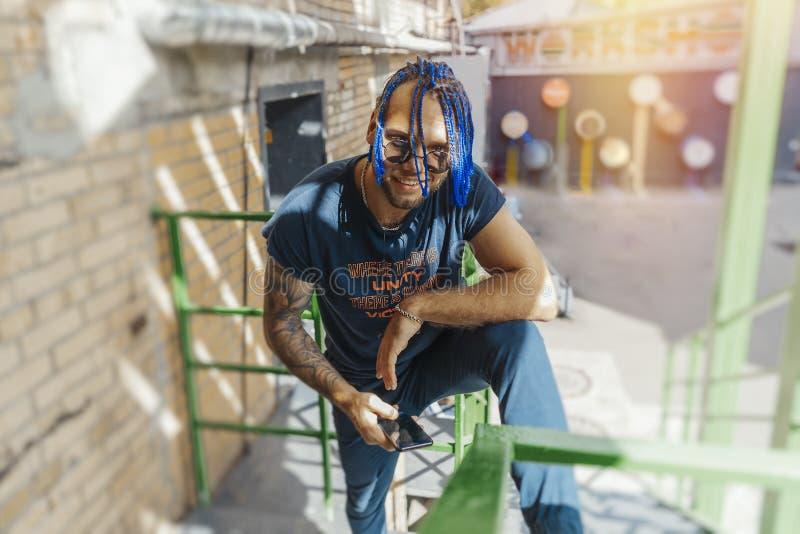 Hombre joven con los dreadlocks azules que se colocan en las escaleras verdes fotografía de archivo
