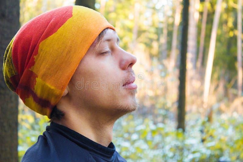 Hombre joven con los ojos cerrados en bosque fotografía de archivo