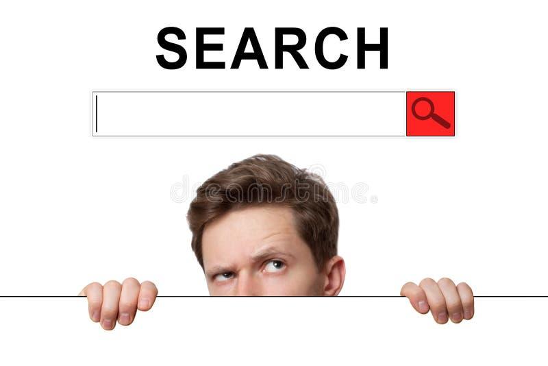 """Hombre joven con los ojos sorprendidos que miran a escondidas hacia fuera de detrás la cartelera en búsqueda de la inscripción """" fotografía de archivo"""