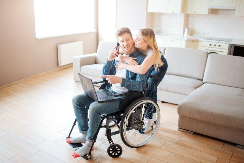Hombre joven con necesidades especiales así como mujer hermosa Él se sienta en ordenador portátil de la silla de ruedas y del  foto de archivo libre de regalías