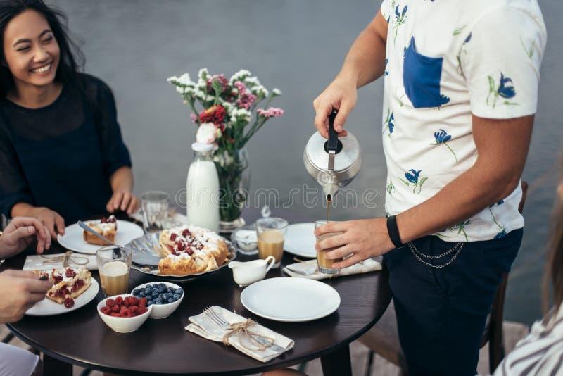 Hombre joven con té de colada de la tetera en la taza durante rotura amistosa fotografía de archivo