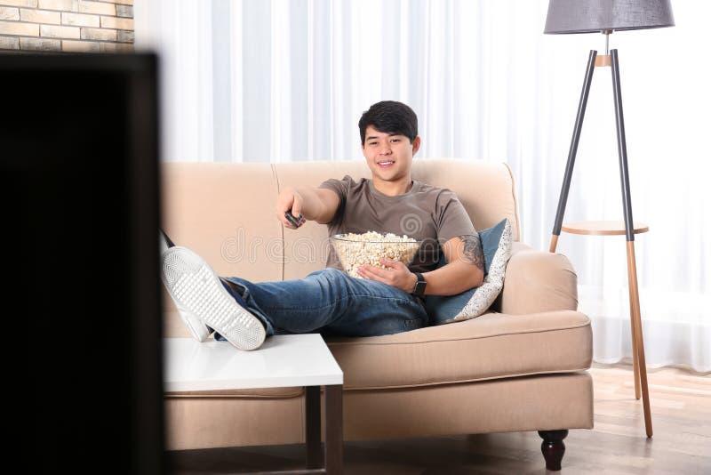 Hombre joven con teledirigido y cuenco de palomitas que ve la TV imagen de archivo