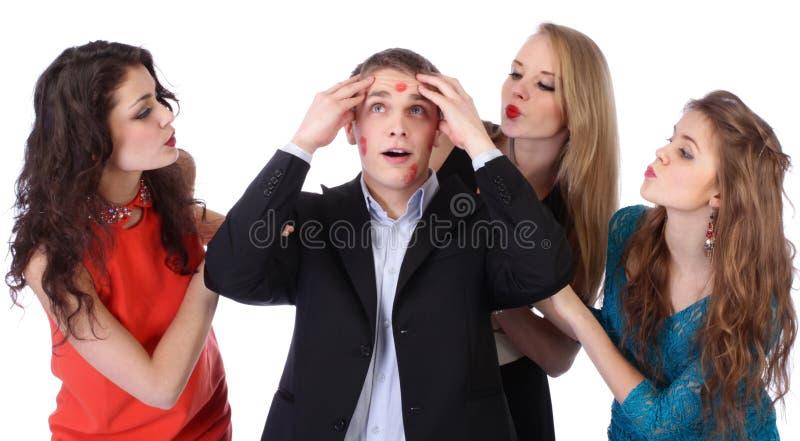 Hombre joven con tres muchachas y beso-marcas del lápiz labial fotos de archivo libres de regalías