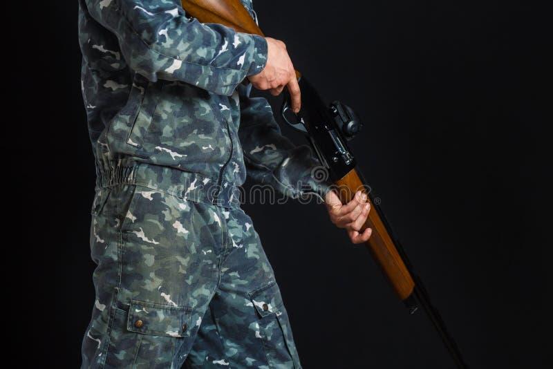 Hombre joven con un arma Un soldado en uniforme militar con una escopeta Juegos de guerra Preparaci?n para la primavera, caza del imagenes de archivo