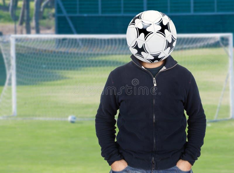 Hombre joven con un balón de fútbol en vez de la cabeza foto de archivo libre de regalías