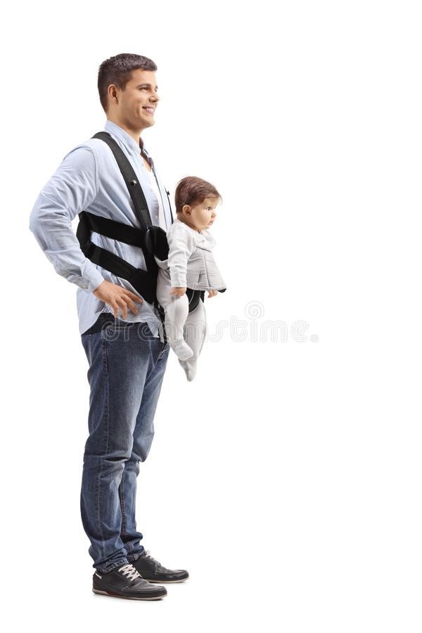 Hombre joven con un bebé en un portador que se coloca y que sonríe imagenes de archivo
