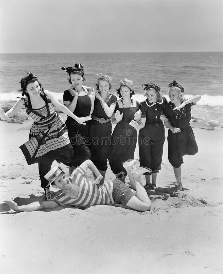 Hombre joven con un grupo de mujeres jovenes en la playa (todas las personas representadas no son vivas más largo y ningún estado imagen de archivo libre de regalías