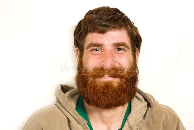 Hombre joven con una barba roja que sonríe sobre cámara fotografía de archivo