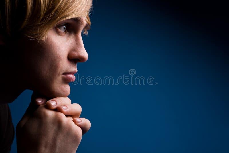 Hombre joven con una mirada seria sobre azul fotografía de archivo libre de regalías