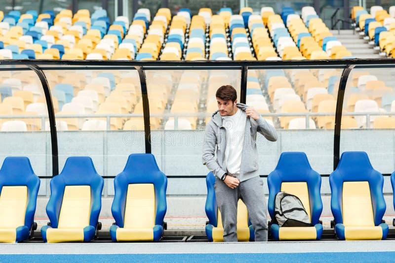 Hombre joven concentrado de los deportes en el estadio foto de archivo