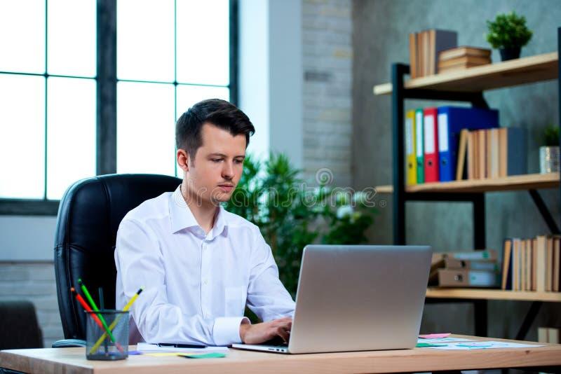 Hombre joven concentrado del encargado que se sienta en el escritorio de oficina que trabaja en el ordenador portátil, mecanograf imagen de archivo
