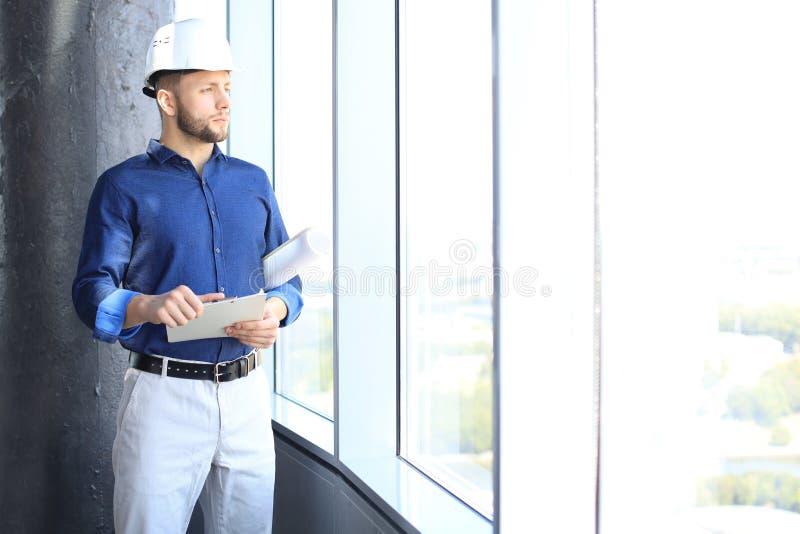Hombre joven confiado en modelo y la mirada de la tenencia del casco de protección lejos mientras que se coloca dentro fotos de archivo libres de regalías