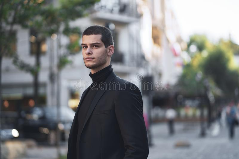 Hombre joven confiado que camina en una calle europea de la ciudad foto de archivo