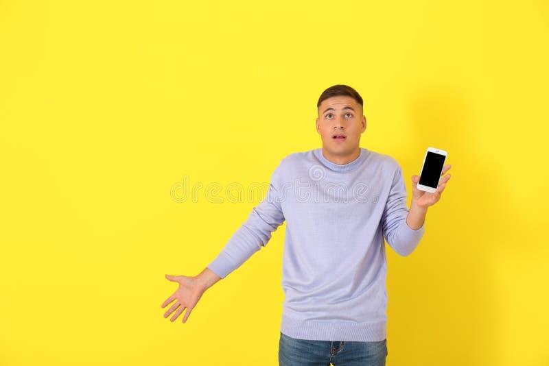 Hombre joven confuso con el teléfono móvil inoperable en fondo del color foto de archivo