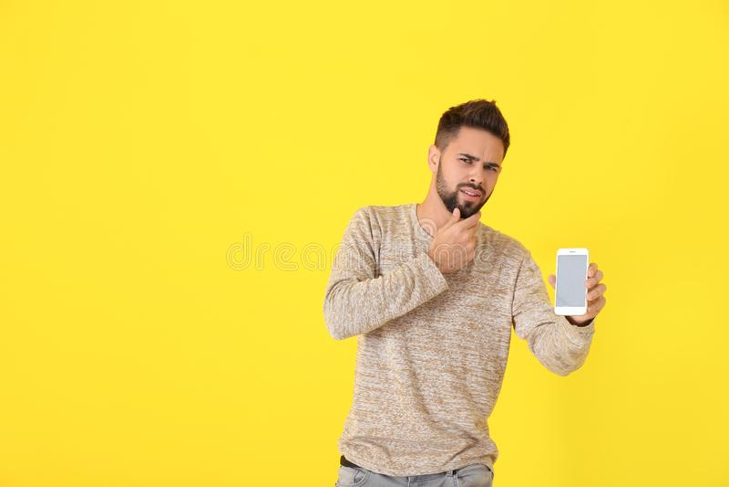 Hombre joven confuso con el teléfono móvil inoperable en fondo del color imágenes de archivo libres de regalías