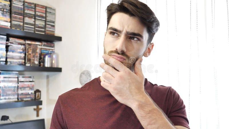 Hombre joven confuso o dudoso que rasguña su barbilla imagen de archivo libre de regalías