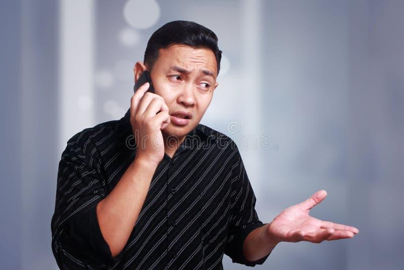 Hombre joven confuso que habla en su teléfono imagen de archivo