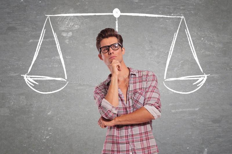 Hombre joven confuso que reflexiona todas las opciones imagenes de archivo