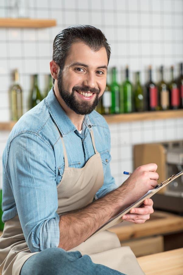 Hombre joven creativo que sonríe mientras que escribe un menú para un café foto de archivo