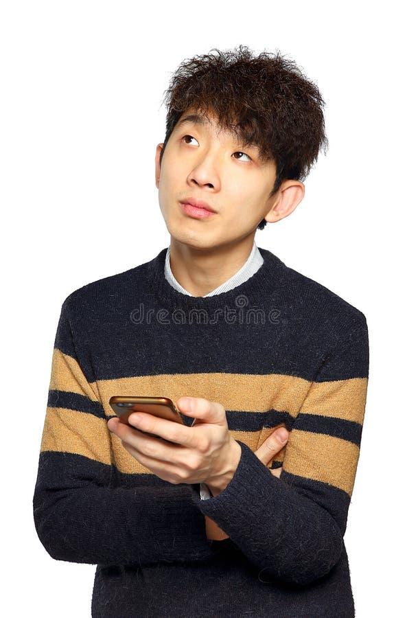 Hombre joven de Asia que manda un SMS en el móvil imagenes de archivo