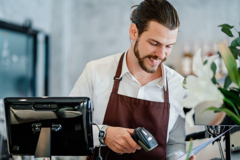 Hombre joven de Barista que explora código o el código de barras de QR en papel del menú en el contador en cafetería Nuevo concep imagenes de archivo