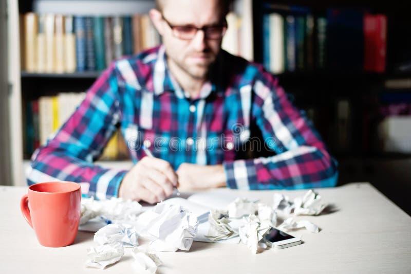 Hombre joven de Blured que trabaja y que piensa en la biblioteca imágenes de archivo libres de regalías