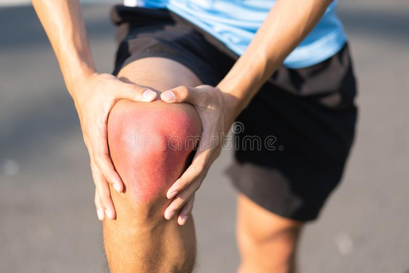 Hombre joven de la aptitud que lleva a cabo su lesión en la pierna de los deportes músculo doloroso durante el entrenamiento Corr fotografía de archivo libre de regalías