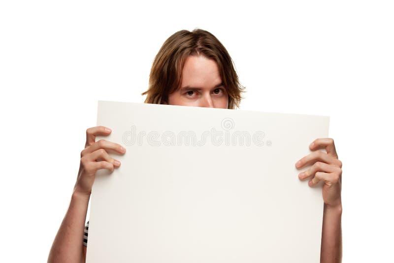 Hombre joven de la diversión que lleva a cabo la muestra blanca en blanco foto de archivo libre de regalías