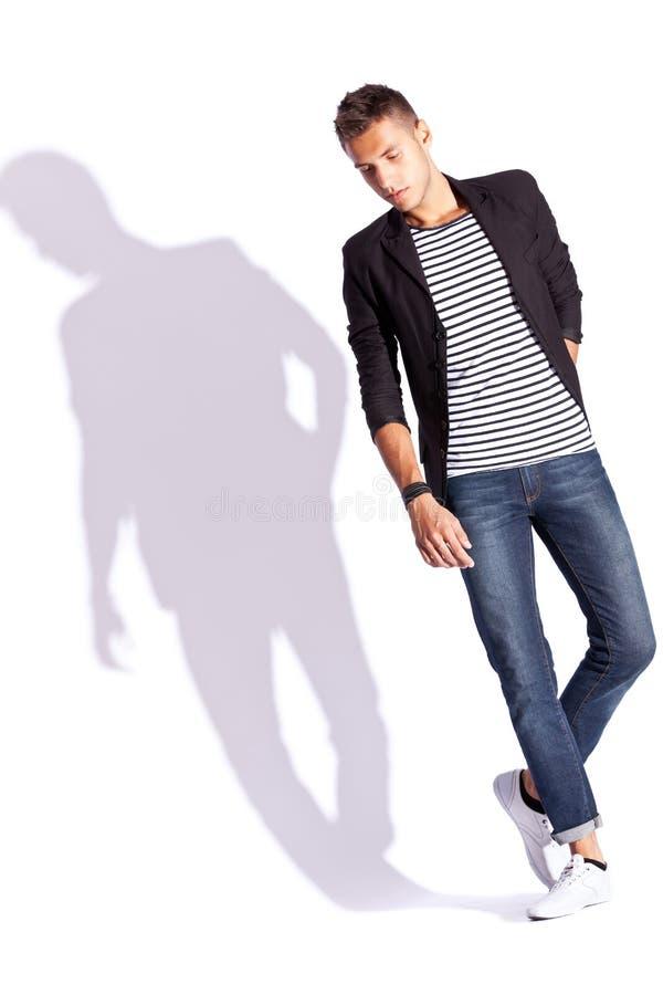 Hombre joven de la manera en camisa, capa y pantalones vaqueros imagen de archivo