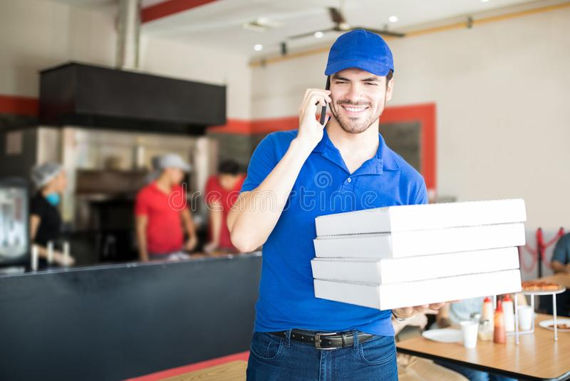 Hombre joven de la pizza que toma una orden sobre el teléfono en tienda de pizza fotografía de archivo libre de regalías