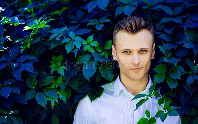 Hombre joven de moda hermoso que se coloca en las hojas de un salvaje imagenes de archivo