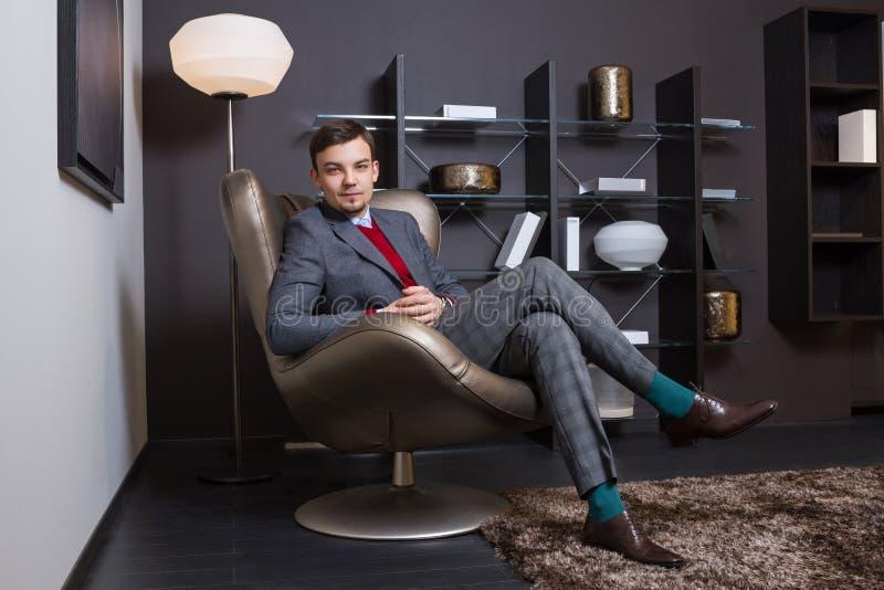 Hombre joven de moda que se sienta en una silla fotos de archivo