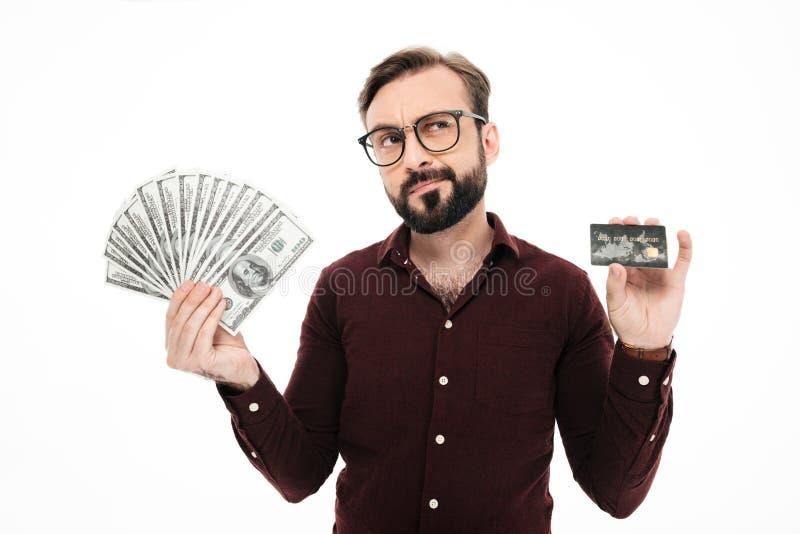 Hombre joven de pensamiento confuso que sostiene la tarjeta del dinero y de crédito imagen de archivo