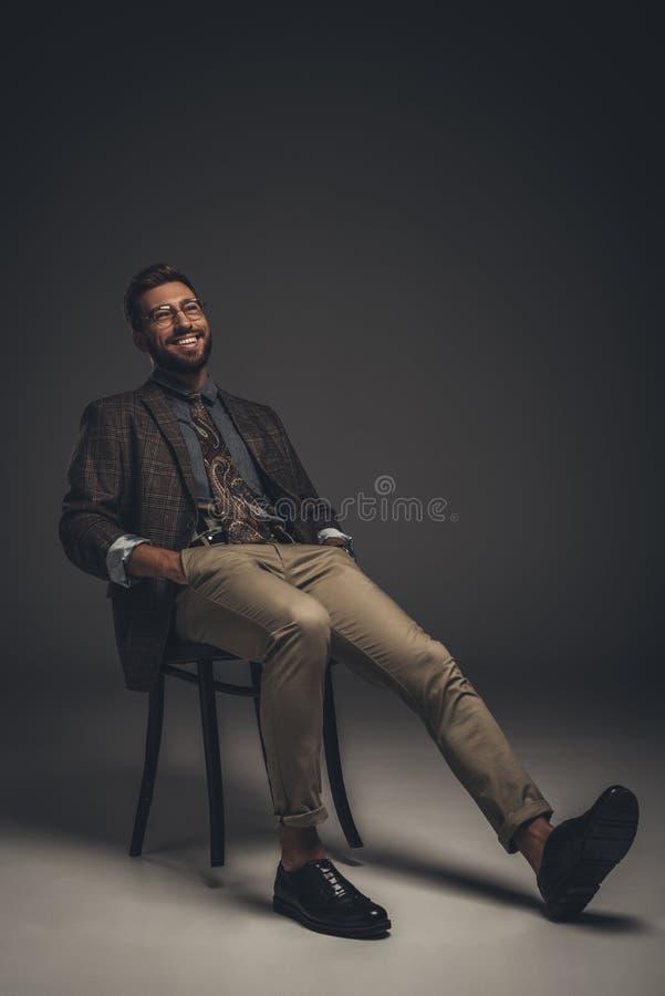 Hombre joven de risa en el traje y los vidrios que se sientan en silla con las manos fotografía de archivo