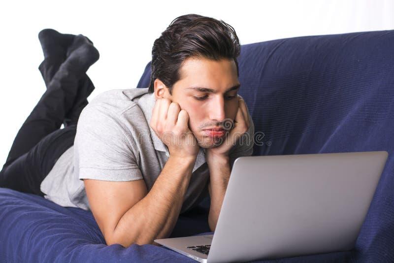 Hombre joven decepcionado o aburrido que mira fijamente la PC del ordenador portátil imagenes de archivo