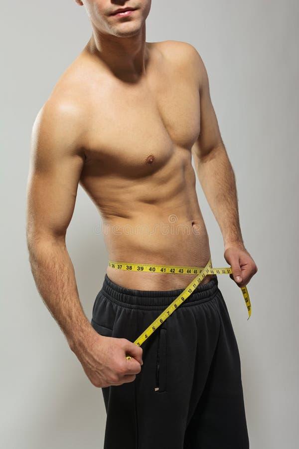 Hombre joven del ajuste descamisado que mide su cintura imágenes de archivo libres de regalías
