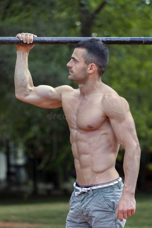 Hombre joven del ajuste hermoso que hace ejercicios en la barra horizontal y imagenes de archivo